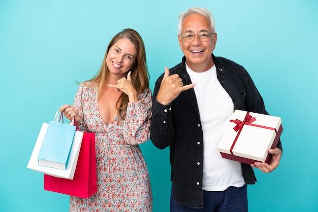 Couple d'âge moyen avec panier et cadeau isolé sur fond bleu faisant un geste téléphonique. rappelle-moi signe