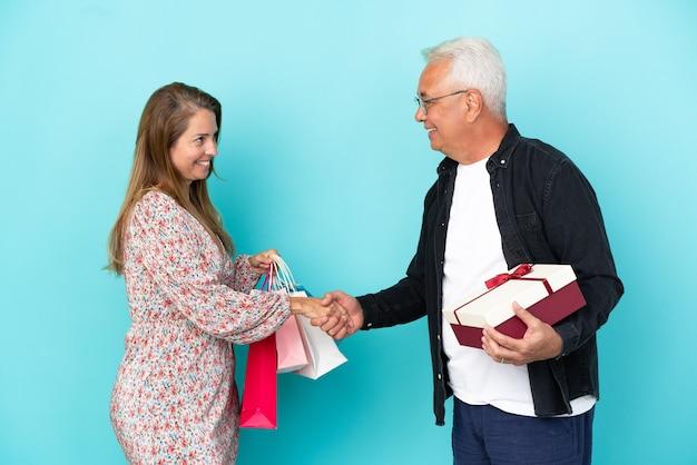 Couple d'âge moyen avec panier et cadeau isolé sur fond bleu poignée de main après une bonne affaire