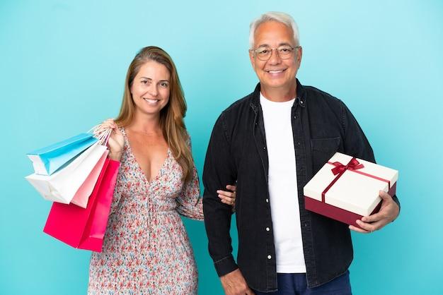 Couple d'âge moyen avec panier et cadeau isolé sur fond bleu posant avec les bras à la hanche et souriant