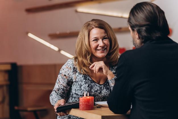 Un couple d'âge moyen à une table dans un café le jour de la saint-valentin