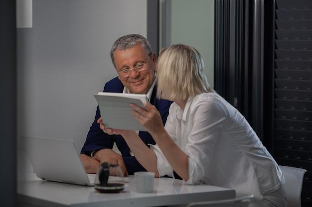 Un couple d'âge moyen à la table avec leurs appareils