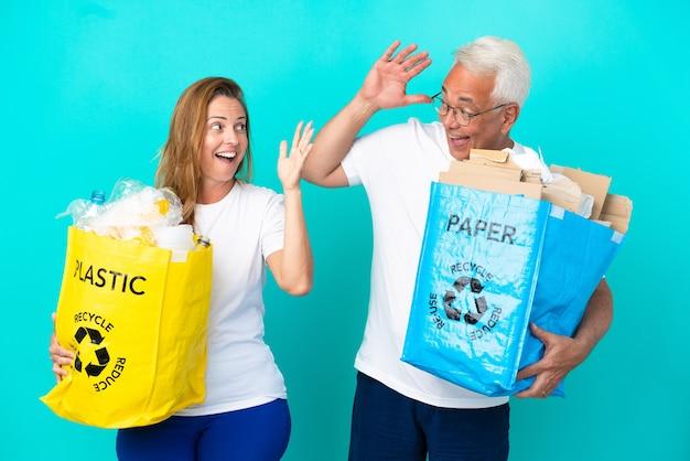 Couple d'âge moyen tenant un sac de recyclage plein de papier et de plastique isolé sur fond blanc avec une expression faciale surprise et choquée