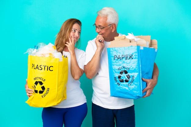 Couple d'âge moyen tenant un sac de recyclage plein de papier et de plastique isolé sur fond blanc se regardant