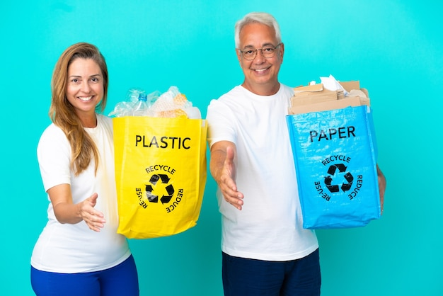 Couple d'âge moyen tenant un sac de recyclage plein de papier et de plastique isolé sur fond blanc se serrant la main pour conclure une bonne affaire
