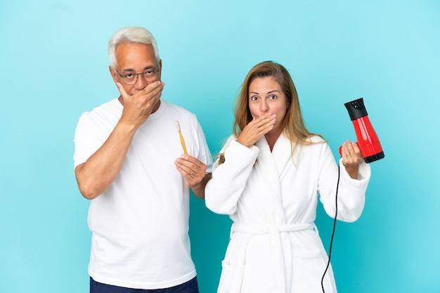 Couple d'âge moyen tenant une sécheuse et une brosse à dents isolées sur fond bleu couvrant la bouche avec les mains pour avoir dit quelque chose d'inapproprié