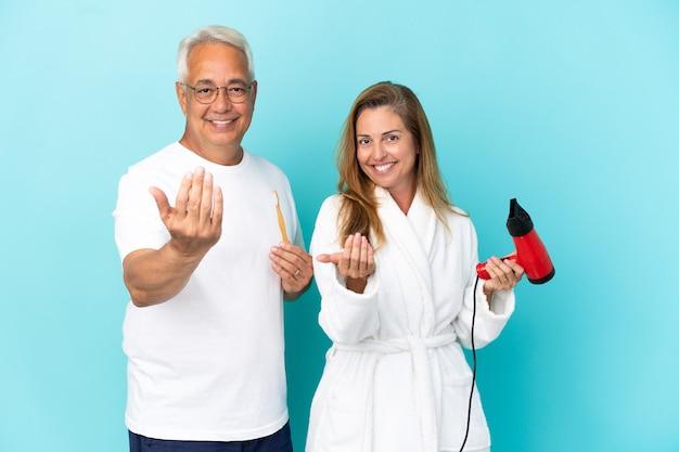 Couple d'âge moyen tenant une sécheuse et une brosse à dents isolées sur fond bleu invitant à venir avec la main. heureux que tu sois venu