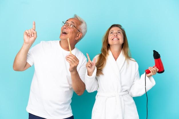 Couple d'âge moyen tenant une sécheuse et une brosse à dents isolées sur fond bleu pointant avec l'index une excellente idée
