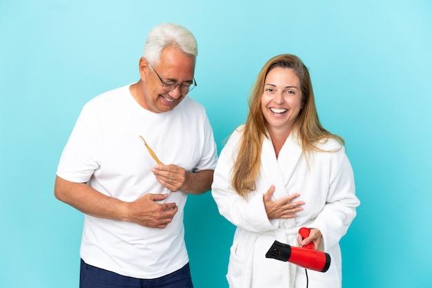 Couple d'âge moyen tenant une sécheuse et une brosse à dents isolées sur fond bleu souriant beaucoup tout en mettant les mains sur la poitrine