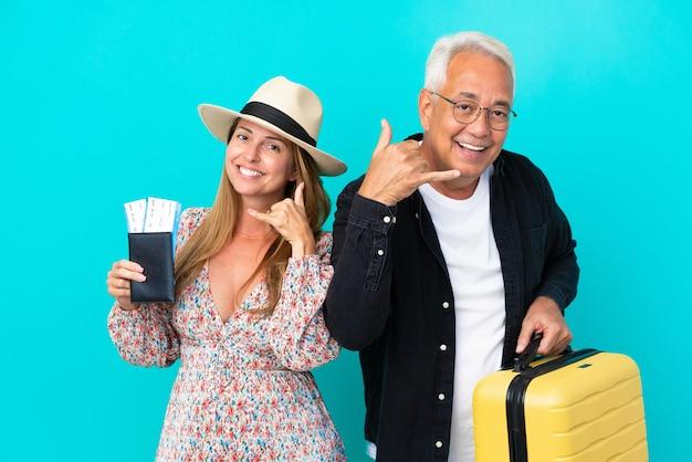 Couple d'âge moyen va voyager et tenant une valise isolée sur fond bleu faisant un geste téléphonique. rappelle-moi signe