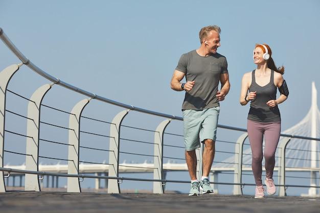 Couple d'âge mûr actif positif dans les écouteurs se regardant tout en faisant du jogging ensemble sur le remblai
