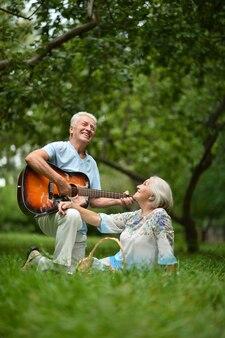 Couple d'âge mûr aimant avec guitare dans le parc d'été