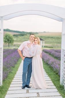 Couple d'âge mûr amoureux debout à l'extérieur sous l'arche en bois dans un champ de lavande, passant un rendez-vous romantique et une célébration d'anniversaire. concept de mariage, d'amour et de famille