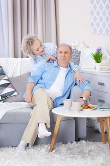 Couple d'âge mûr assis ensemble sur un canapé à la maison