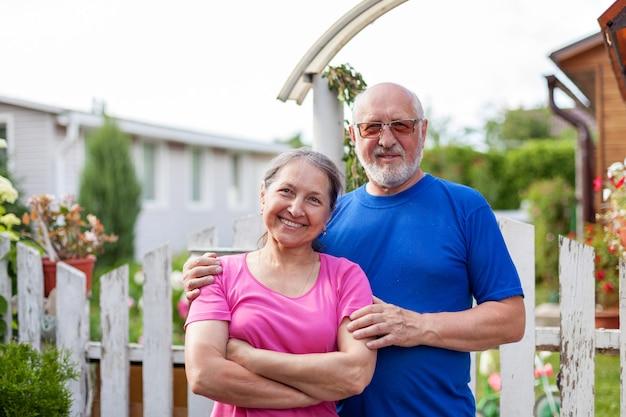 Couple d'âge mûr au portillon de maison de village