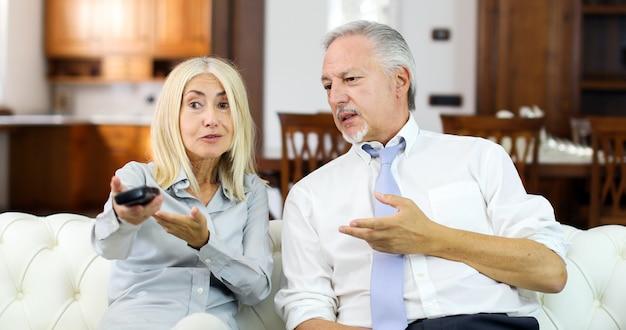Couple d'âge mûr ayant des arguments en regardant la télévision