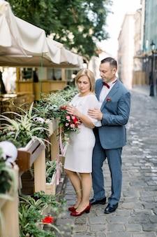 Couple d'âge mûr dans des vêtements à la mode, posant près de décorations de pots de fleurs au café de la ville en plein air