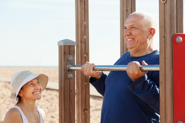 Couple d'âge mûr de formation avec barre de traction