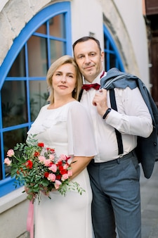 Couple d'âge mûr heureux, étreignant dehors dans la ville, posant près de belles fenêtres bleues de cru
