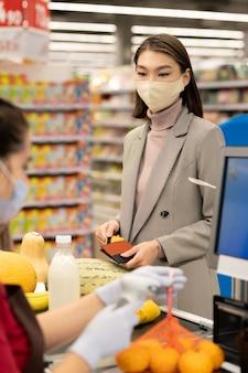 Couple d'âge mûr joyeux debout près de la caisse enregistreuse devant un jeune caissier métis scannant ce qu'ils ont acheté au supermarché