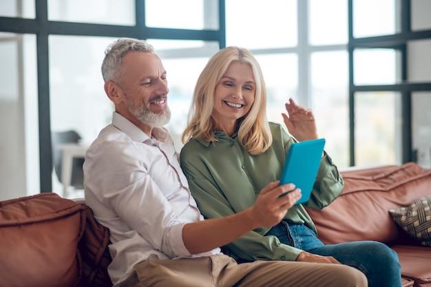 Couple d'âge mûr à lunettes de soleil assis sur le canapé et ayant un appel vidéo