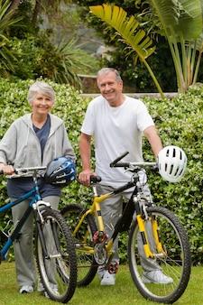 Couple d'âge mûr marchant avec leurs vélos