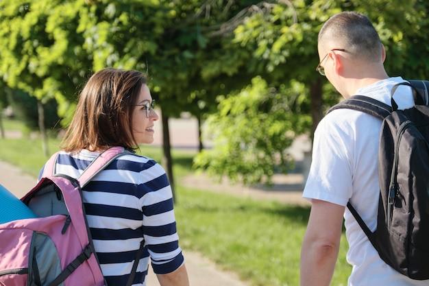 Couple d'âge mûr marchant et parlant homme et femme, personnes vêtues de vêtements de sport allant à la formation de remise en forme, mode de vie sain et actif et relations de 40 ans