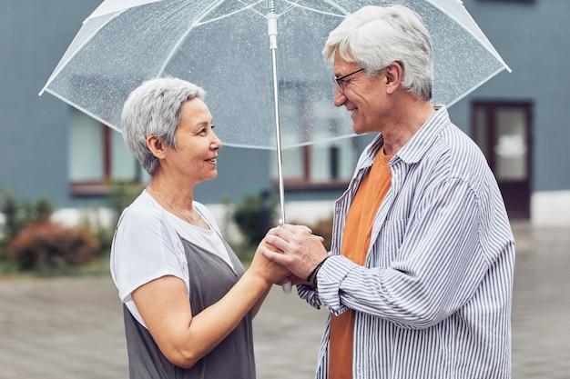 Couple d'âge mûr moderne sous parapluie