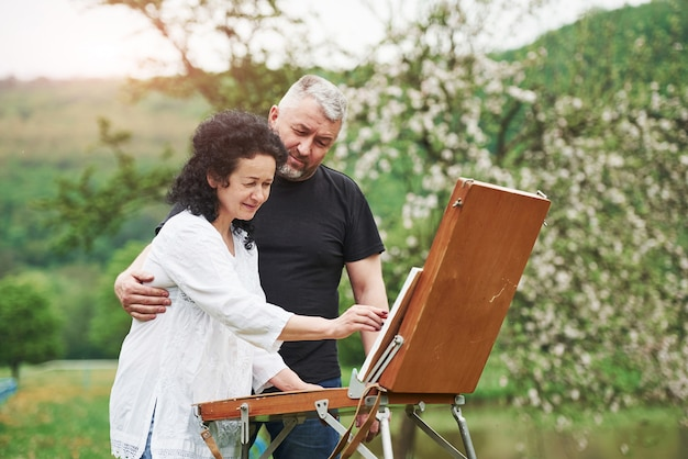 Couple d'âge mûr ont des journées de loisirs et travaillent ensemble sur la peinture dans le parc