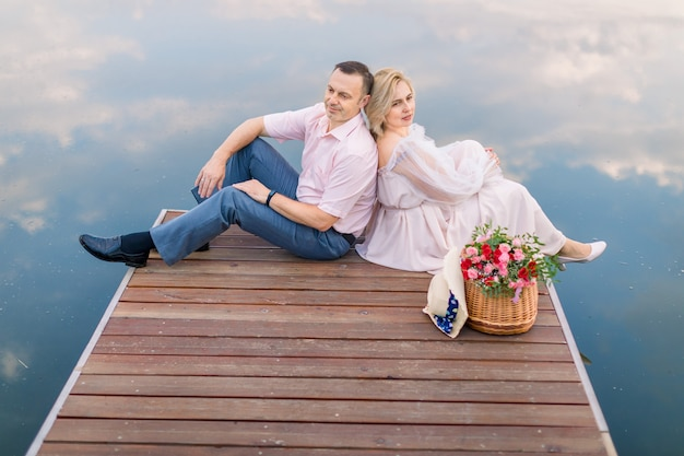 Couple d'âge mûr paisible et rêveur assis dos à dos sur le pont pont en bois au bord de la rivière ou de l'étang