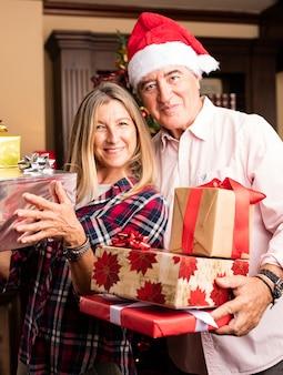 Couple d'âge mûr posant avec de nombreux cadeaux
