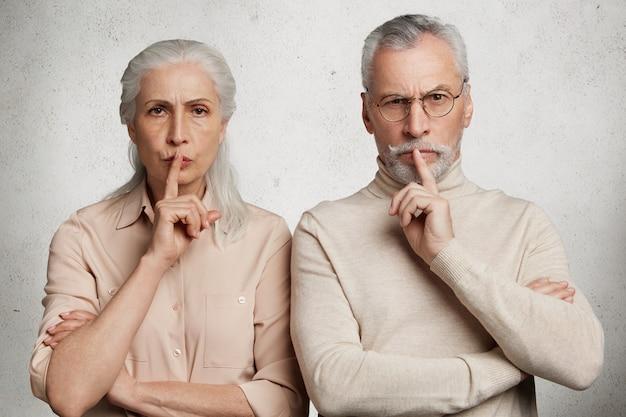 Couple d'âge mûr pose contre le mur de béton blanc