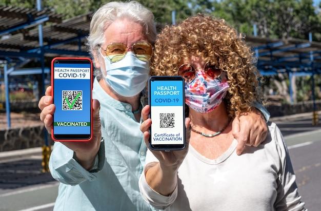 Couple d'âge mûr prêt à voyager montrant une certification de santé numérique pour les personnes vaccinées contre le coronavirus