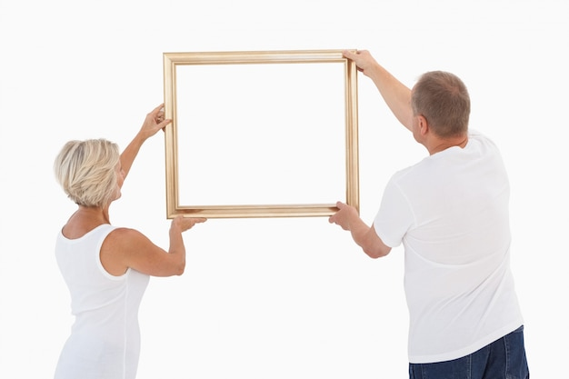 Couple d'âge mûr raccrochant cadre
