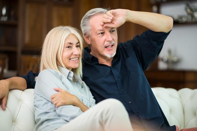 Couple d'âge mûr en regardant une émission de télévision ensemble