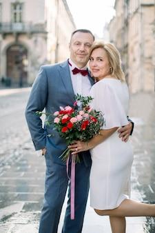 Couple d'âge mûr romantique dans l'ancienne ville européenne. portrait en gros plan d'un bel homme de 50 ans et de sa jolie charmante femme amoureuse, debout dans la rue et souriant à la caméra