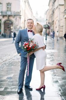 Couple d'âge mûr romantique dans l'ancienne ville européenne. portrait en pied d'un homme et d'une femme amoureux, debout dans la rue. une femme en robe tient un bouquet de fleurs et embrasse son mari