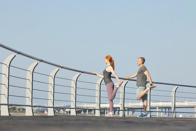 Couple d'âge mûr sportif debout à la balustrade et étirement des jambes tout en s'entraînant ensemble