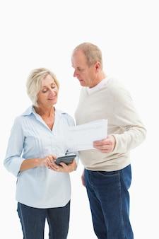 Couple d'âge mûr travaillant sur leurs factures