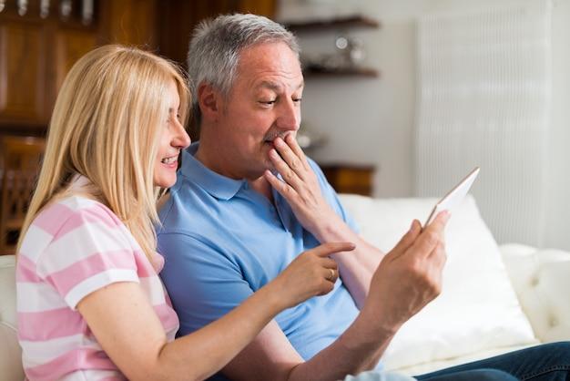 Couple d'âge mûr utilisant une tablette numérique dans leur appartement