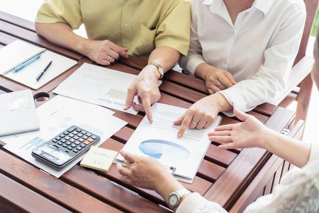 Couple âgé positif consultant avec un agent d'assurance présente des données d'analyse les tableaux et graphiques