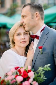 Couple d'âge romantique sensuel avec bouquet de fleurs, debout l'un à côté de l'autre à l'extérieur de la ville