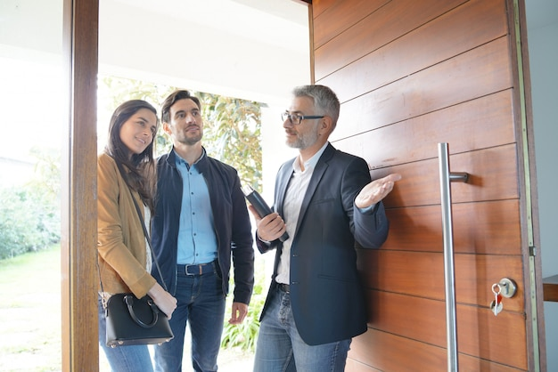Couple avec agent immobilier visitant une maison moderne