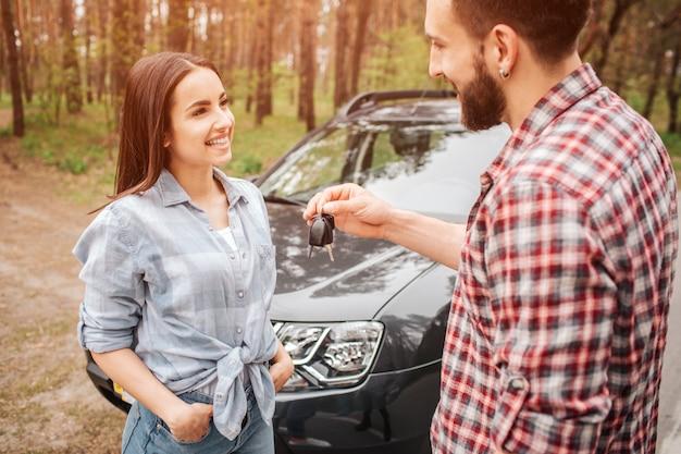 Couple agréable et charmant stansing près d'une voiture noire dans la forêt. guy et fille se regardent et sourient. il lui donne les clés de la voiture.