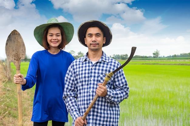 Couple d'agriculteurs asiatiques tenant des outils dans la riziculture en thaïlande