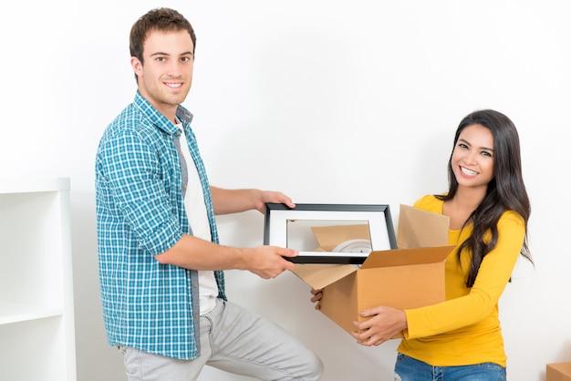 Couple aidant les uns les autres emménageant dans une nouvelle maison