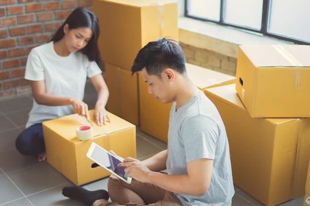 Couple aidant emballer les produits commandés en ligne des clients.