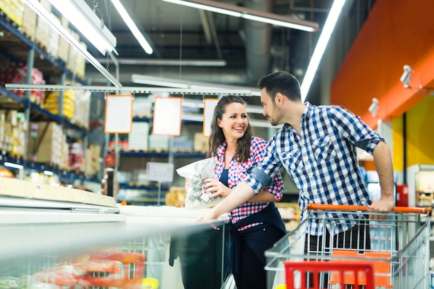 Couple à l'aide d'achats de chariot en magasin pour la nourriture et les ingrédients