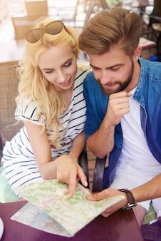 Couple à l'aide d'une carte papier lors d'une visite touristique