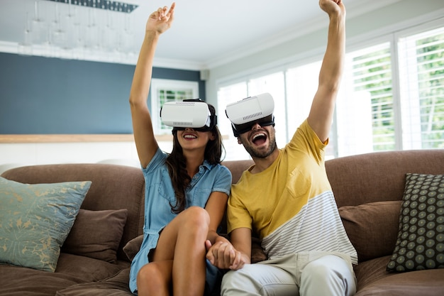 Couple à l'aide d'un casque de réalité virtuelle dans le salon à la maison