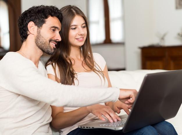 Couple à l'aide de leur ordinateur portable à la maison